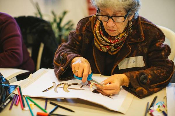 Fotografia de senhora preparando estêncil para grafitagem