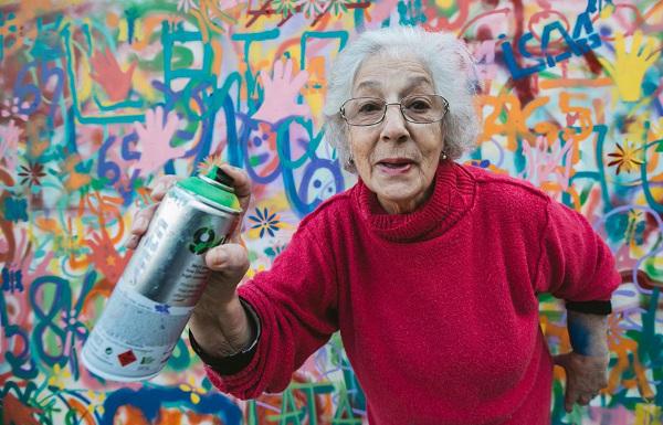 fotografia da parede grafitada com senhora à frente.
