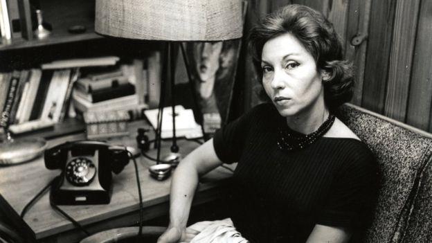 Fotografia mostra Clarice Lispector sentada em uma poltrona, olhando para a câmera. Seu braço está sobre uma escrivaninha com telefone e abajur. Ao fundo, diversos livros em uma estante.
