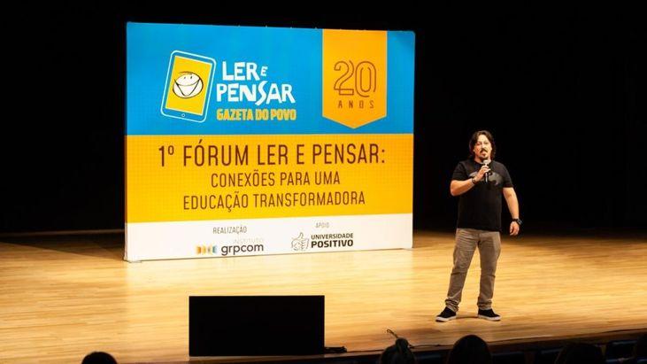 Fotografia de José Motta Filho diante de um banner com os dizeres