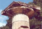 """Coluna dórica (ou capitel dórico) do Templo de Hera (c. 550 a.C.), em Olímpia. O templo grego é uma das tipologias de maior relevo na arquitetura da Grécia Antiga. Tem origem no """"mégaron"""", um espaço existente nos anteriores palácios micênicos, exercendo uma forte influência na posterior arquitetura da Roma Antiga e no seu respectivo templo romano. A maioria dos templos gregos clássicos eram hexastilos (fachada com seis colunas). Sua área era composta pelo Pronaos (antecâmara que antecede o naos e que se transformará, mais tarde, no nártex), Naos ou Cella (neste espaço, delimitado por 4 paredes sem janelas, é colocada a estátua da divindade e pode ser, por vezes, organizado em 3 alas divididas por colunas. Em templos de grandes dimensões o naos pode funcionar como um pátio interior, sem cobertura), Aditon ou Abaton (espaço só acessível a sacerdotes para o culto ou colocação de oferendas. Esta área pode funcionar de diferentes maneiras; como uma sub-divisão do naos, aberta para ele; como uma câmara isolada no centro do naos; ou como um nicho na parede posterior do naos) e Opistódomo (câmara oposta ao pronaos onde se encontra o tesouro e que também pode funcionar, por vezes, como aditon). <br> <br> Palavras-chave: Hera, coluna, capitel, dórico, clássico, Olímpia, arquitetura, estética"""